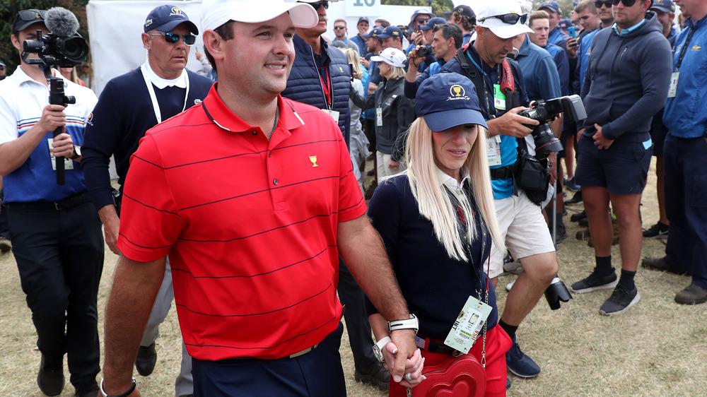 Patrick Reed y Justine Reed caminando de la mano, ambos con sombreros, rodeados de fotógrafos y fanáticos.