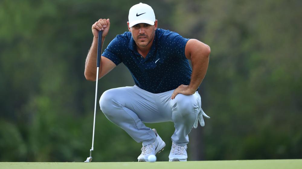Brooks Koepka en cuclillas en un campo de golf