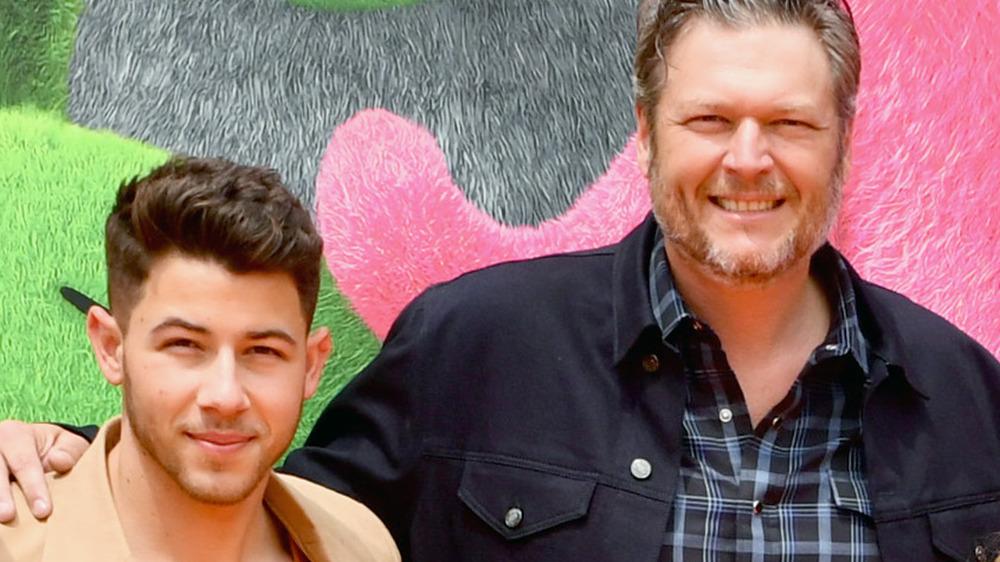 Nick Jonas y Blake Shelton sonriendo en la alfombra roja
