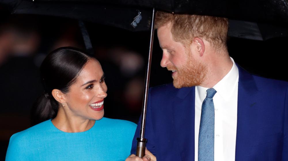 Meghan Markle y el príncipe Harry riendo bajo el paraguas