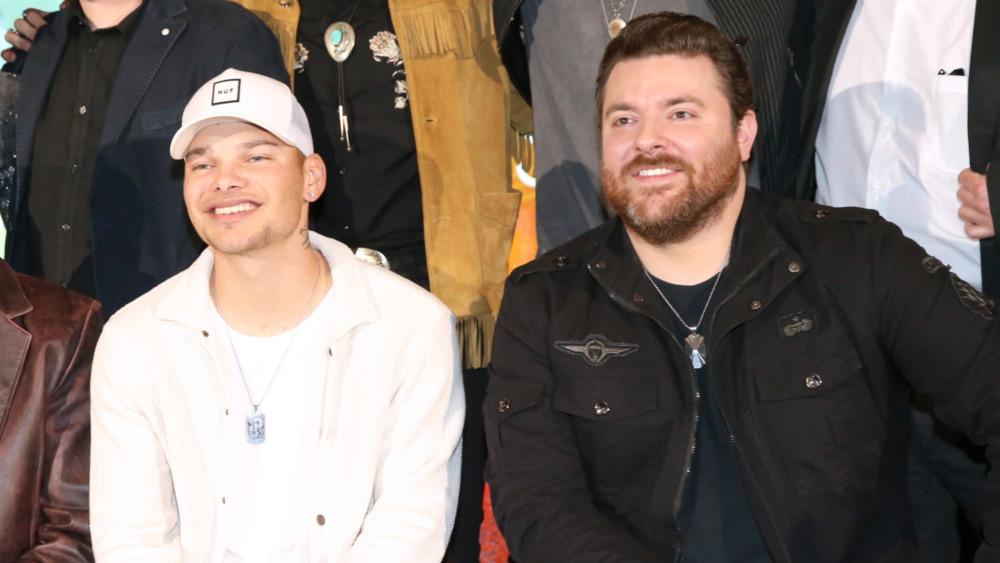 Kane Brown y Chris Young sonríen juntos mientras posan en un evento