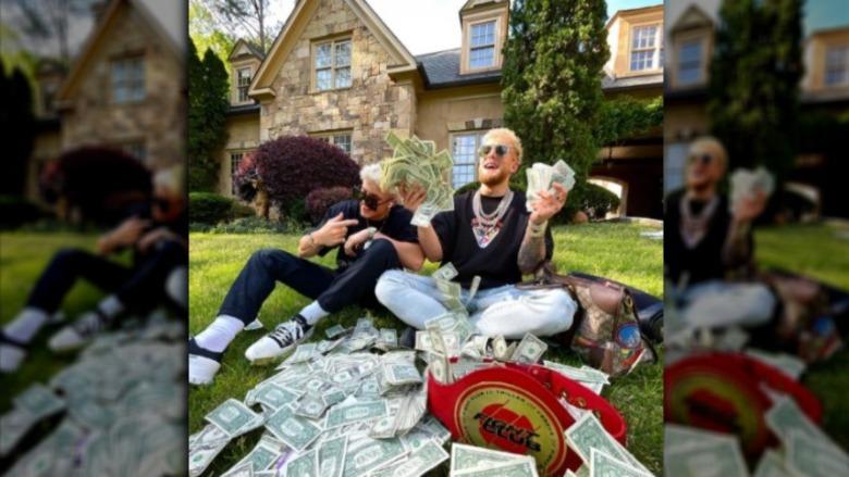 Jake Paul con gafas de sol en el jardín delantero de una casa con billetes de un dólar en la mano junto a un compañero no identificado