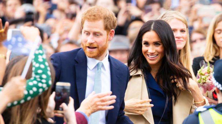 El príncipe Harry y Meghan Markle saludan a una multitud