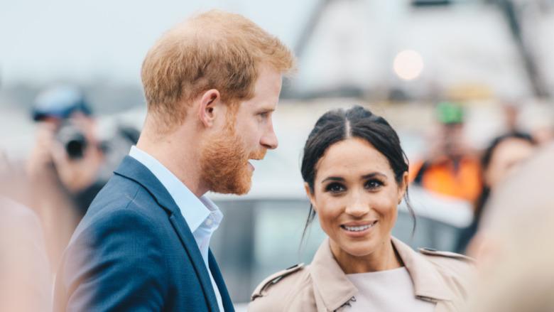 El príncipe Harry y Meghan Markle sonriendo entre una multitud