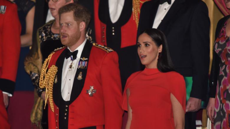 El príncipe Harry y Meghan Markle de pie con la boca abierta