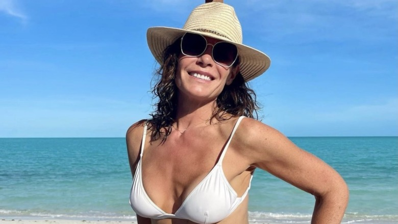 Luann de Lesseps, sonriente, vistiendo un bikini blanco, gafas de sol, gorro de playa, en la playa, el océano detrás de ella
