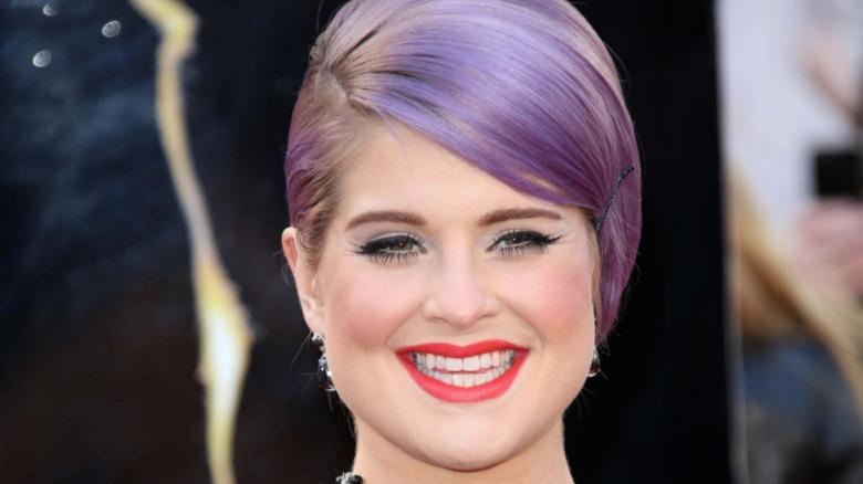 Kelly Osbourne sonriendo lápiz labial rojo cabello morado