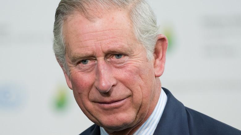 El príncipe Carlos sonríe con picardía en un evento