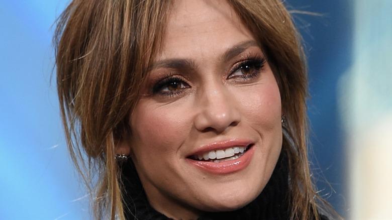 Jennifer Lopez sonriendo y mirando hacia un lado