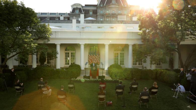Jardín de rosas de la Casa Blanca con reporteros sentados en sillas socialmente distanciadas