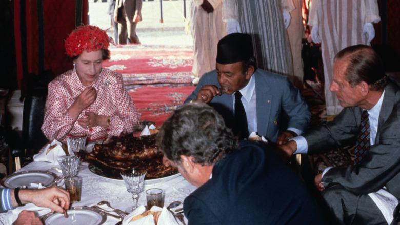La reina Isabel comiendo con las manos mirando infeliz