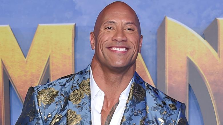 Dwayne Johnson sonriendo en la alfombra roja