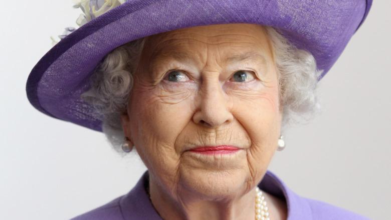 La reina Isabel II con un sombrero morado