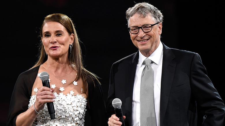 Melinda y Bill Gates hablando y sonriendo sosteniendo micrófonos