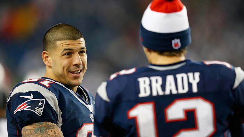 Aaron Hernandez hablando con Tom Brady en el campo