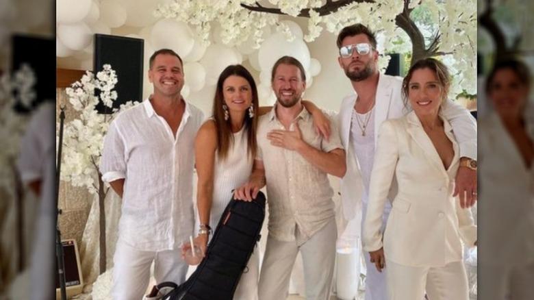 Amigos de Chris Hemsworth y Elsa Pataky (extremo derecho respectivamente) posando juntos y sonriendo con atuendos completamente blancos.