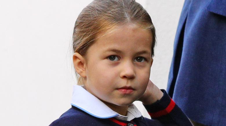 Princesa Charlotte tocándose el pelo y mirando hacia arriba