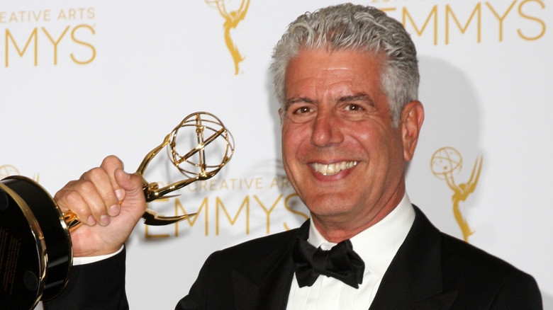 Anthony Bourdain sonriendo y sosteniendo un Emmy