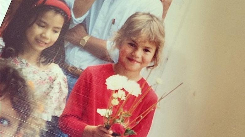 Chrissy Teigen de niña sosteniendo flores