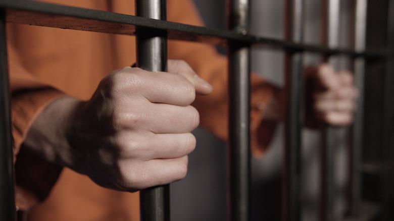 manos tras las rejas en la cárcel