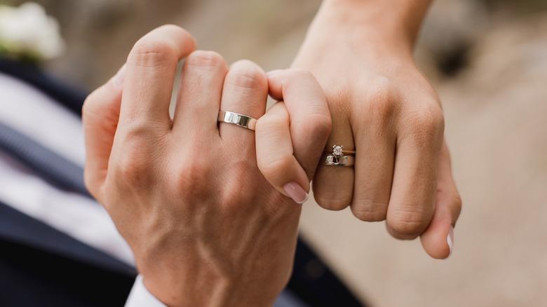 Manos de la pareja casada, con meñiques entrelazados