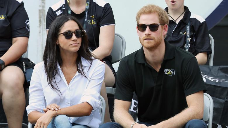 Meghan Markle Príncipe Harry sentado y con gafas de sol