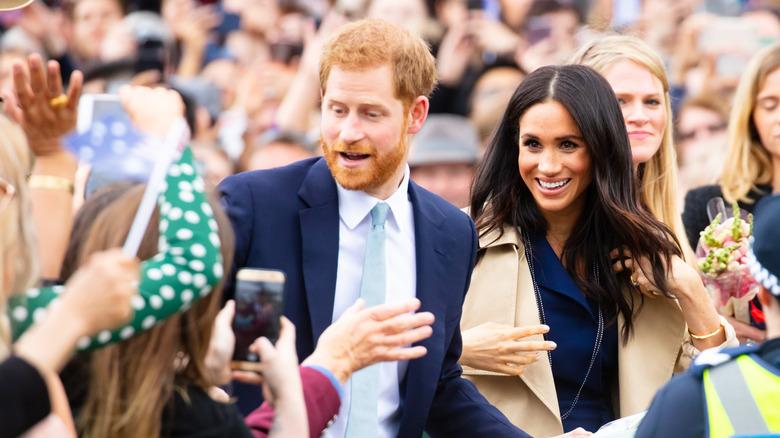 El príncipe Harry y Meghan Markle sonríen entre la multitud