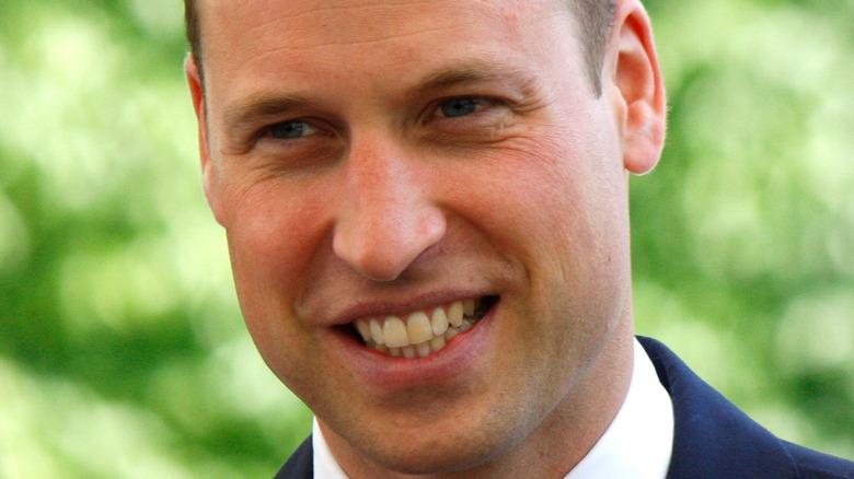 El príncipe William sonriendo con la cabeza ligeramente inclinada.