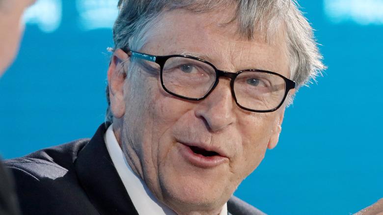 Bill Gates hablando y mirando a su lado derecho con un par de anteojos.