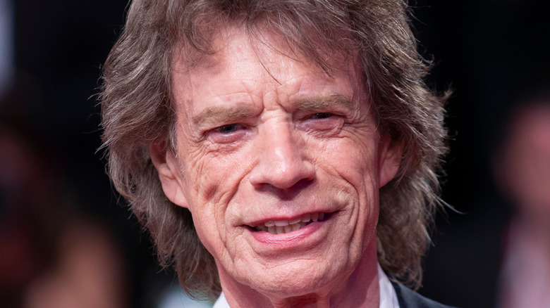Mick Jagger sonríe con un traje oscuro.