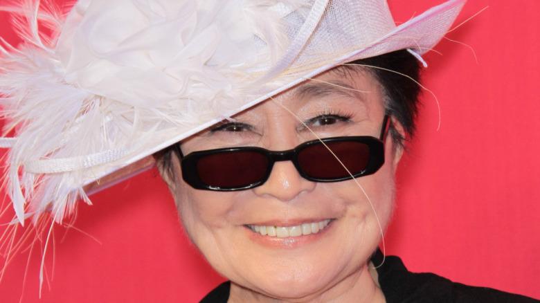 Yoko Ono sonriendo con gafas de sol y un sombrero de plumas
