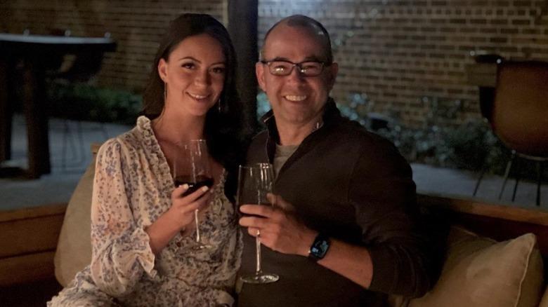Melyssa Davies y James Murray sonriendo con copas de vino