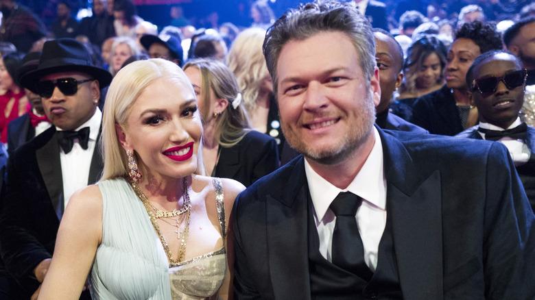 Gwen Stefani y Blake Shelton sentados y posando