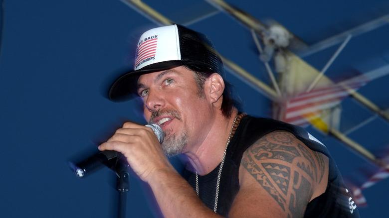 Tim Medvetz sosteniendo un micrófono
