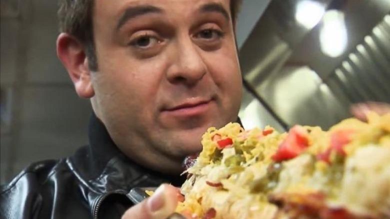Adam Richman sosteniendo comida