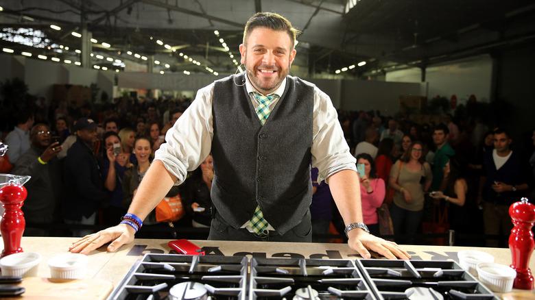 Adam Richman sonriendo en un evento de cocina