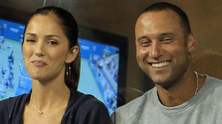 Minka Kelly y Derek Jeter sonriendo en un juego de pelota