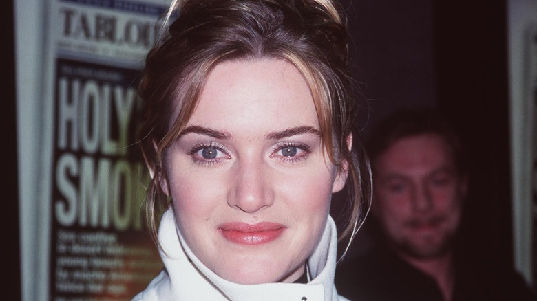 Kate Winslet con una chaqueta blanca, posando