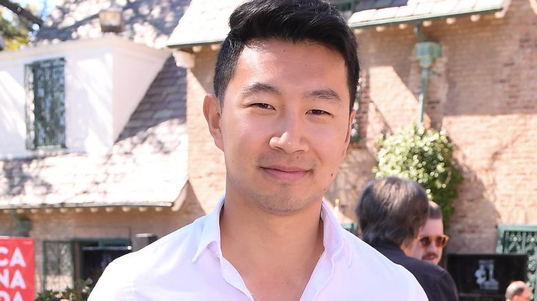 Simu Liu sonriendo con una camisa blanca