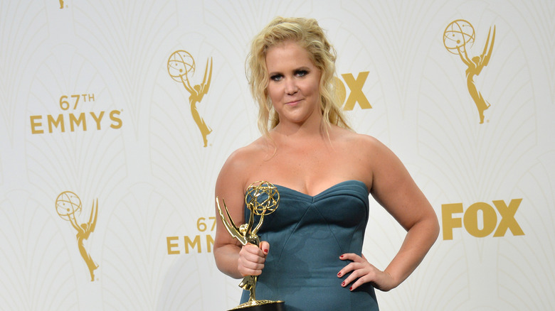 Amy Schumer sosteniendo un Emmy