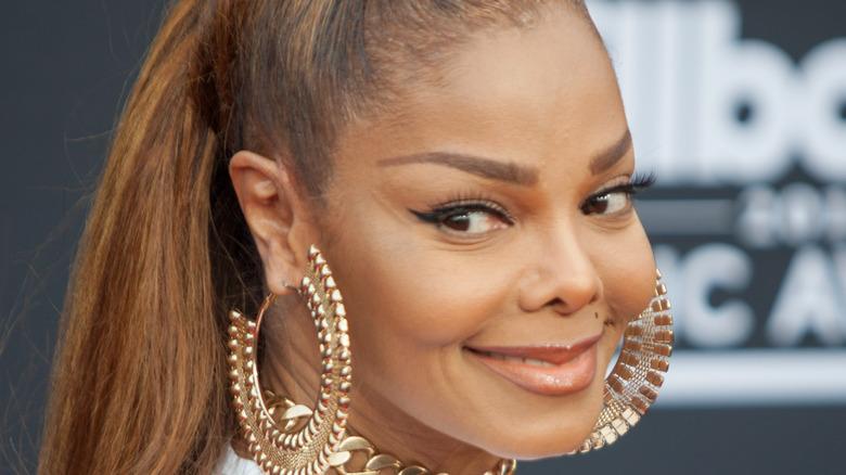 Janet Jackson sonriendo por encima del hombro