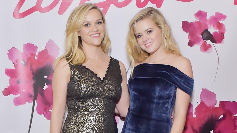 Reese Witherspoon con vestido dorado y Ava Phillippe con vestido azul