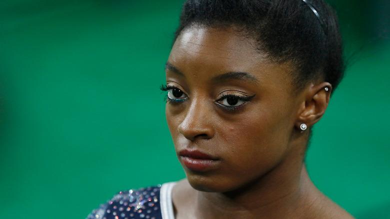 Simone Biles con expresión seria durante la competición