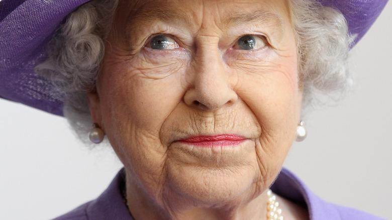 La reina Isabel con sombrero morado