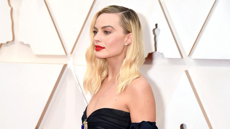 Margot Robbie posando de lado en la alfombra roja