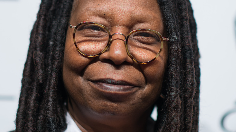 Whoopi Goldberg sonríe con gafas de carey.