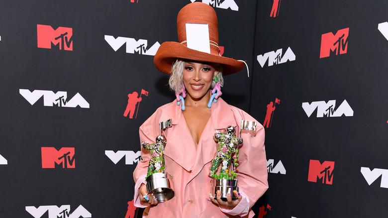 Doja Cat sonriendo y sosteniendo VMAs con sombrero grande