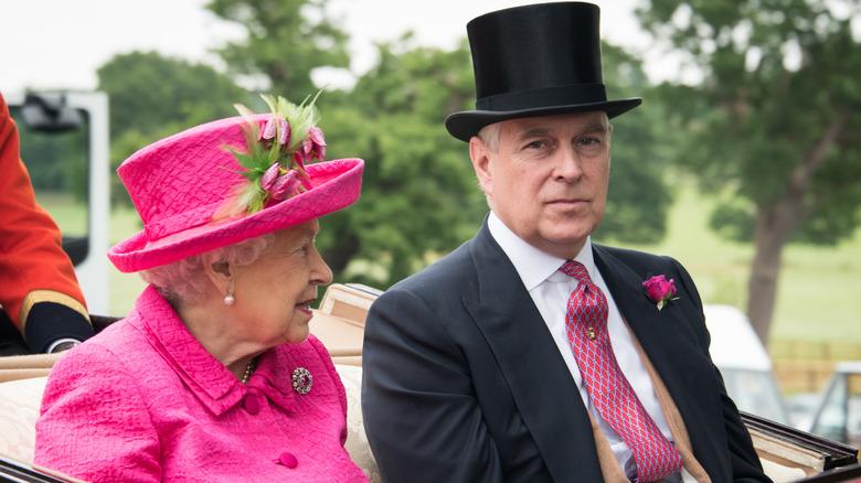 la reina isabel y el príncipe andrés vestidos en un coche