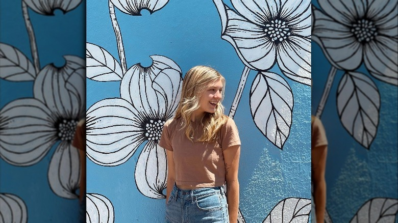 Gabby Petito sonriendo con mural floral en segundo plano.