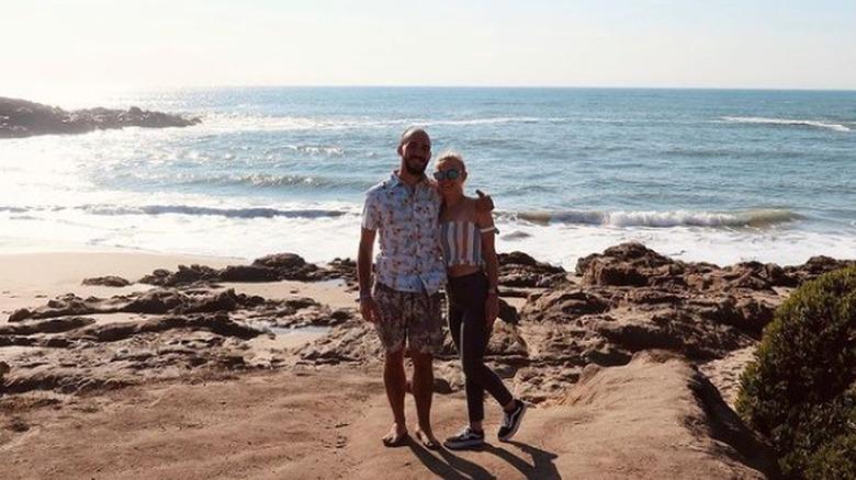 Brian Laundrie y Gabby Petito sonriendo con agua de fondo